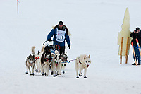 Musher Blake Freking and his Siberian Husky team runs up the ramp from the Bering Sea onto Front Street in Nome during the 2010 Iditarod
