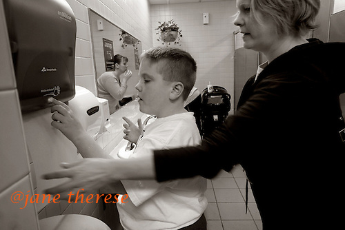 "After finishing lunch at the mall, Drew and Jill use the bathroom. Jill helps Drew wash his hands after using the bathroom in the ladies restroom. ""I wish places had more 'family restrooms'. Drew is too old to be going into the womens bathroom and I can't let him go into the mens bathroom all alone."" Drew who is severely autistic, needs help with even the most basics of care. photo by jane therese"