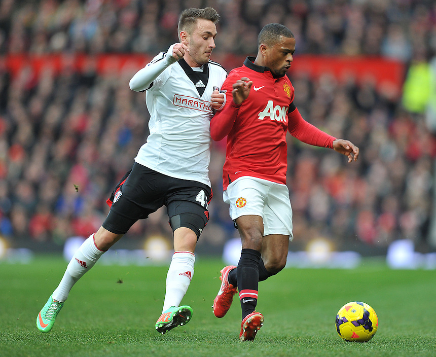Manchester United's Patrice Evra shields the ball from Fulham's Muamer Tankovic<br /> <br /> Photo by Dave Howarth/CameraSport<br /> <br /> Football - Barclays Premiership - Manchester United v Fulham - Sunday 9th February 2014 - Old Trafford - Manchester<br /> <br /> &copy; CameraSport - 43 Linden Ave. Countesthorpe. Leicester. England. LE8 5PG - Tel: +44 (0) 116 277 4147 - admin@camerasport.com - www.camerasport.com