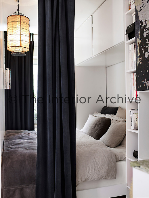 Built-in cupboards and shelving create a niche around the bed, utilising the limited space