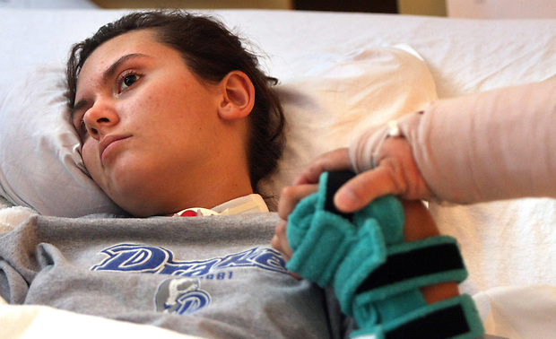 Mike Cassler holds the hand of his daughter, Elizabeth while in prayer over her bed at Blank Children's Hospital.   Elizabeth is recovering from a severe brain injury she sustained in an auto accident.  Once an elite soccer player, she has emerged from a drug-induced coma and is in the process of re-learning all of her motor skills.