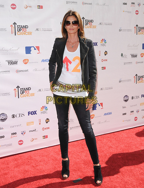 CINDY CRAWFORD .at Stand Up to Cancer held at Sony Picture Studios in Culver City, California, USA, September 10th 2010.     .full length white t-shirt jacket jeans ankle boots cork platform  sunglasses biker leather chains belt                                                                    .CAP/RKE/DVS.©DVS/RockinExposures/Capital Pictures.