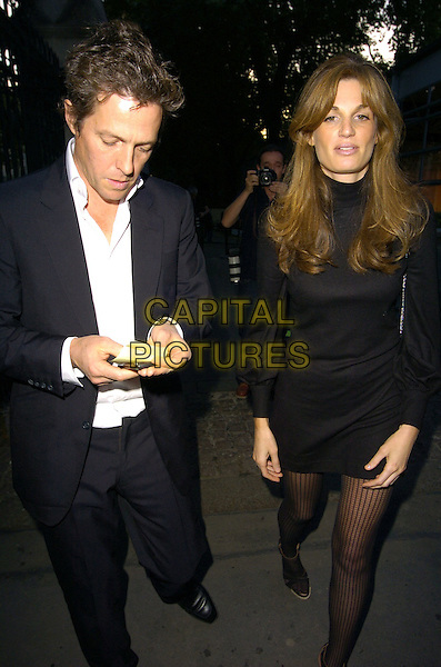 HUGH GRANT & JEMIMA KHAN .At the BIBA Spring/Summer 2007 Catwalk Show during London Fashion Week, BFc Tent, Natural Hitsory Museum, London, England, September 19th 2006..full length goldsmith suit jacket white shirt black mini dress polo neck patterned tights walking .Ref: CAN.www.capitalpictures.com.sales@capitalpictures.com.©Can Nguyen/Capital Pictures