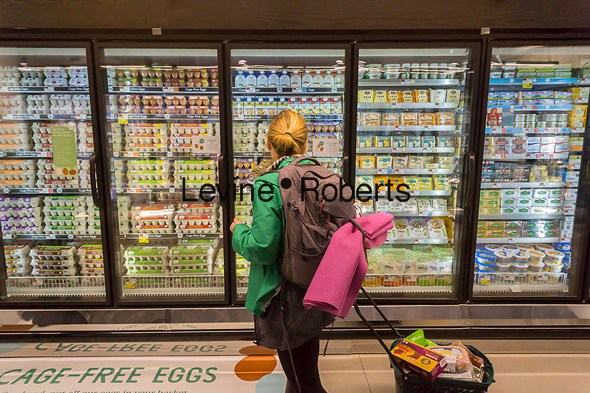 A shopper chooses cafe-free eggs in a cooler in the new Whole Foods Market in Newark, NJ on opening day Wednesday, March 1, 2017. The store is the chain's 17th store to open in New Jersey. The 29,000 square foot store located in the redeveloped former Hahne & Co. department store building is seen as a harbinger of the revitalization of Newark which never fully recovered from the riots in the 1960's.  (© Richard B. Levine)