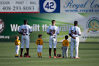San Jose Giants outfielders Jacob Heyward (33), Bryce Johnson (28), and Sandro Fabian (54) stand alongside Little League baseball players during the National Anthem before a California League game against the Modesto Nuts at San Jose Municipal Stadium on May 15, 2018 in San Jose, California. Modesto defeated San Jose 7-5. (Zachary Lucy/Four Seam Images)