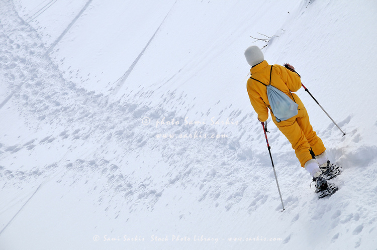 Woman snowshoeing, French Alps, France