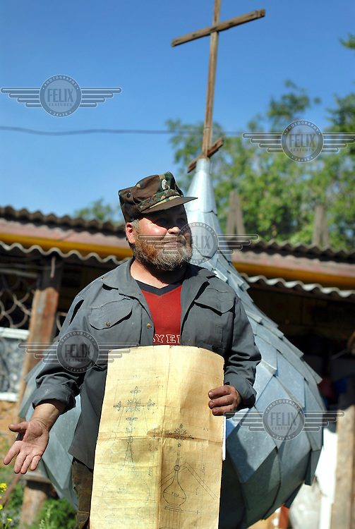 Anatoly, an ethnic Cossack, carpenter by trade and a member of the congregation at a Russian Orthodox church. He holds plans for the new dome he is working on for his church.