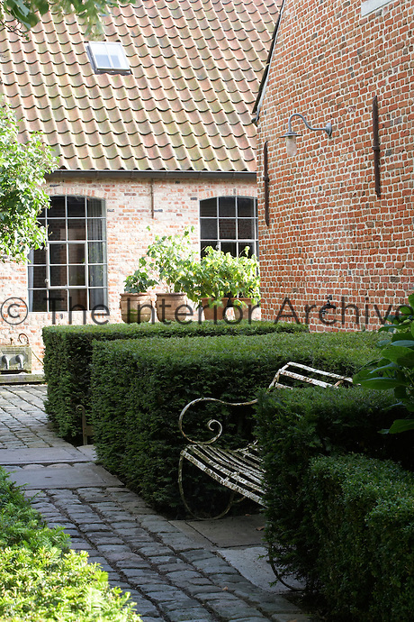 The traditional rear courtyard of the 19th century farmhouse with its brick paths and box hedging