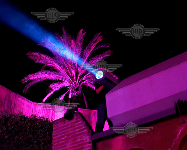 A spotlight shines across an outside space at the Olivia Valere discoteque and restaurant in Marbella. A palm tree is lit up in bright pinnk in the background. The city of Marbella on Spain´s southern coast has become an oasis of luxury and indulgence in a country deeply affected by the crippling economic crisis that has led to widespread foreclosures and an unemmployment rate of over 26%. The city's sunny weather and extensive tourist infrastructure complete with a marina for yachts and numerous golf courses has become a magnet for Russian and Gulf money.