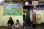 Local restaurant, Bumthang town, Bhutan..Bhutan the country that prides itself on the development of 'Gross National Happiness' rather than GNP. This attitude pervades education, government, proclamations by royalty and politicians alike, and in the daily life of Bhutanese people. Strong adherence and respect for a royal family and Buddhism, mean the people generally follow what they are told and taught. There are of course contradictions between the modern and tradional world more often seen in urban rather than rural contexts. Phallic images of huge penises adorn the traditional homes, surrounded by animal spirits; Gross National Penis. Slow development, and fending off the modern world, television only introduced ten years ago, the lack of intrusive tourism, as tourists need to pay a daily minimum entry of $250, ecotourism for the rich, leaves a relatively unworldly populace, but with very high literacy, good health service and payments to peasants to not kill wild animals, or misuse forest, enables sustainable development and protects the country's natural heritage. Whilst various hydro-electric schemes, cash crops including apples, pull in import revenue, and Bhutan is helped with aid from the international community. Its population is only a meagre 700,000. Indian and Nepalese workers carry out the menial road and construction work.
