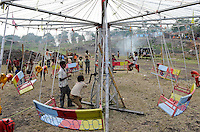 INDIA Jharkhand Dhanbad Jharia , children in carousel , background smoke of burning underground coal seams, children work as coal picker / INDIEN Kohlerevier Dhanbad / Jharia , Kinder im Karussell auf einem Jahrmarkt vor brennenden Kohlefloezen, Kinder sammeln Kohle in Abraumhalden um Geld fuer die Familie zu verdienen