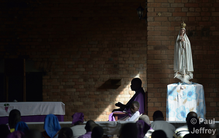 A priest sits during mass in the Catholic Church in Riimenze, South Sudan.
