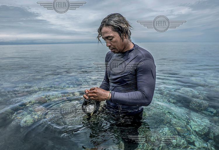 Marjono Lessing (35) rubs a sea sponge over his mask to prevent it from steaming up before a spearfishing session near the Bajau stilt-village of Kabalutan.