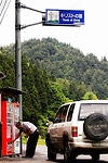 A man buys a drink from a vending machine located beneath a road sign pointing visitors toward Christ's tomb in Shingo Village, Aomori Prefecture, northern Japan. Some residents of Shingo say that Jesus spent 12 years in Japan and is buried in the village. Among them is Sajiro Sawaguchi, who is in his 80s, who claims to be a descendant of Christ and whose family owns the land containing Christ's grave.
