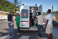 Italy. Lombardy Region. Como. Homeless african migrants live near the San Giovanni railway station. The italian Red Cross from Como has provided an ambulance with some volunteers and offers medical consultation to the migrants. A nurse speaks to a opoliceman while two african migrants are standing on line. The Italian Red Cross (IRC, Italian: Croce Rossa Italiana or CRI) is the Italian national Red Cross society. 11.08.2016 © 2016 Didier Ruef