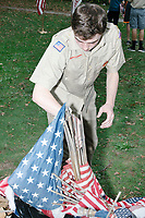 Robert Mountain, age 17, an Eagle Scout candidate, gathers flags for a flag retirement ceremony in Belmont, Massachusetts, USA, on Sat. Oct. 14, 2017. Flag retirement ceremonies are intended to give a dignified end to flags no longer fit to serve as a symbol for the United States of America. The ceremony was organized by Eagle Scout candidate Robert Mountain, 17, of Belmont Boy Scout Troop 66 as his Eagle Scout project.  The ceremony was held in park area surrounding Clay Pit Pond near Belmont High School.