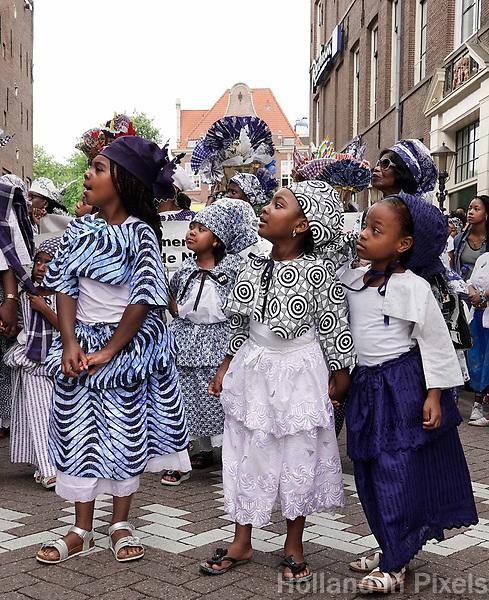 Nederland  Amsterdam - 2018.  Memre Waka optocht door de stad. Op 1 juni wordt in Amsterdam met de herdenkingstocht Memre waka de jaarlijkse Keti koti-maand geopend, die op 1 juli eindigt met de viering van de afschaffing van de slavernij (1 juli 1863). Deze mars wordt georganiseerd door stichting Eer en Herstel en vereniging Opo Kondreman, in samenwerking met onder meer NINSEE en de Black Heritage Tours. Deelnemers aan de tocht krijgen uitleg over huizen die met slavenhandel te maken hadden.   Foto mag niet in negatieve / schadelijke context gebruikt worden.   Foto Berlinda van Dam / Hollandse Hoogte.