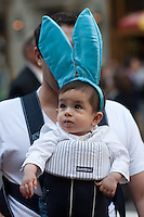 A man holds a baby with bunny ears during the 2011 New York City Easter Parade.