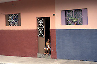 Young girl reading a book while sitting in the doorway of her house in the city of Colima, Mexico