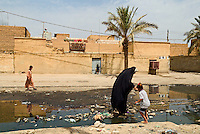 Baghdad, Iraq, June 13, 2003.A boy eats an ice-cream in a street of Saddam City inundated by sewage water. About amillion children live there surrounded by garbage and without access to clean water.