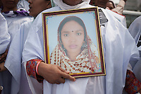 Relative of victims killed in the collapse of Rana Plaza holds the picture of her daughter as she take part in a protest during the second anniversary of the building collapse in Savar, near Dhaka, Bangladesh