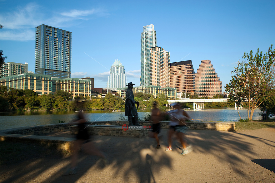 Runners pass the Stevie Ray Vaughan Memorial Statue on Town Lake in downtown Austin, Texas