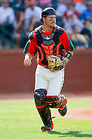 Greensboro Grasshoppers catcher Tony Caldwell (14) follows a play up the first base line during the game against the Delmarva Shorebirds at NewBridge Bank Park on May 26, 2013 in Greensboro, North Carolina.  The Grasshoppers defeated the Shorebirds 11-2.  (Brian Westerholt/Four Seam Images)