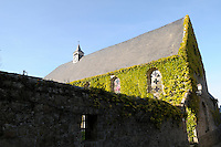 The restored church is overgrown with Virginia creeper and protected by an old stone wall