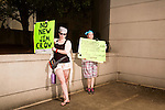 July 13, 2015. Winston Salem, North Carolina.<br />  (left to right) Jennifer Vollmer and Katie Welch wait for the start of the march to support the NC NAACP's voting rights case against Gov. Pat McCrory.<br />  To rally support for the North Carolina NAACP's case against Gov. Pat McCrory (NC NAACP v. McCrory), a march was held in downtown Winston Salem on the opening day of the case in federal court. Thousands gathered to walk the streets of downtown and listen to speeches proclaiming the importance of defeating new requirements for voter registration,<br />  The NC NAACP contests that HB 589 (Voter ID requirements) violate Section 2 of the Voting Rights Act (42 U.S.C. 1973) and the Fourteenth and Fifteenth Amendments of the Constitution.