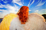Angel with spread wings closeup from behind at dusk. Teen girl angel, with face partly seen in profile, seen waist up from back, with glimpse of water and trees under blue sky with dramatic clouds.