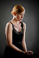 Young red haired woman wearing black dress