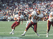 Washington Redskins quarterback Joe Theismann (7) looks to pass during the game against the Los Angeles Raiders at RFK Stadium in Washington, D.C. on October 2, 1983.  Left guard Russ Grimm (68) is blocking for Theismann on the play.  The Redskins won the game 37 - 35.<br /> Credit: Howard L. Sachs / CNP