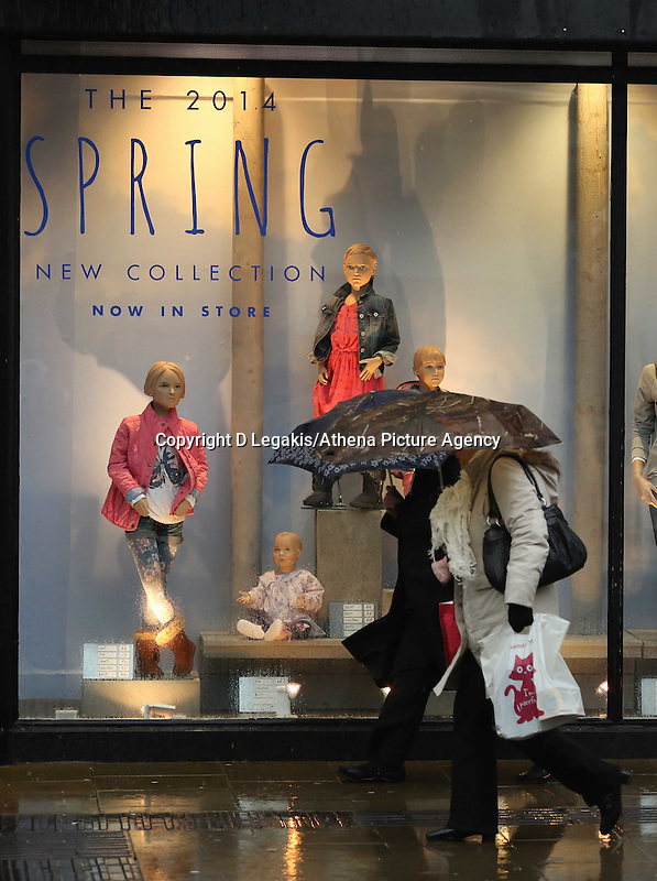 """WEATHER PICTURE WALES<br /> Pictured: Two female shoppers defy the wet weather and walk past a """"Spring Collections"""" shop window in Oxford Street, Swansea, south Wales.<br /> Re: Severe weather has been forecast for parts of the UK for the weekend."""