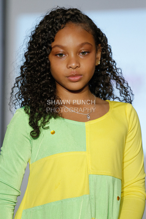 Child model walks runway in an outfit from the Almond Eyez Designs collection, during the KidFash Magazine runway show in Brooklyn, New York on Nov 4, 2017.