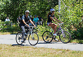 United States President Barack Obama, left, and daughter Malia Obama, right, are followed by security people as they ride their bicycles on the Manuel F. Correllus State Forest bike path outside of West Tisbury, Massachusetts on Friday, August 15,  2014 during their summer vacation.  They were accompanied by and first lady Michelle Obama (not pictured)<br /> Credit: Rick Friedman / Pool via CNP