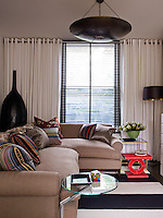 The contemporary living room is elegantly furnished combining colour and texture