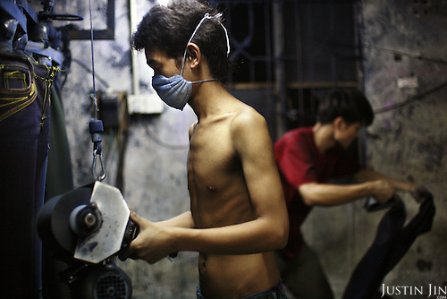 "Workers scrub jeans using a sanding machine in Mr Huang's factory in Zhongshan city, China..This picture is part of a photo and text story on blue jeans production in China by Justin Jin. .China, the ""factory of the world"", is now also the major producer for blue jeans. To meet production demand, thousands of workers sweat through the night scrubbing, spraying and tearing trousers to create their rugged look. .At dawn, workers bundle the garment off to another factory for packaging and shipping around the world..The workers are among the 200 million migrant labourers criss-crossing China.looking for a better life, at the same time building their country into a.mighty industrial power."