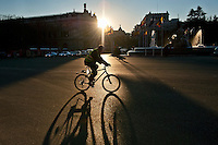 Man riding a bike as the sun rises, Madrid, Spain