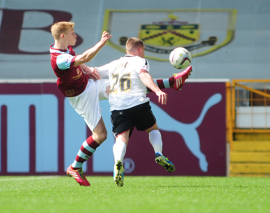 Burnley's Ben Mee vies for possession with Ipswich Town's Paul Taylor <br /> <br /> Photo by Chris Vaughan/CameraSport<br /> <br /> Football - The Football League Sky Bet Championship - Burnley v Ipswich Town - Saturday 26th April 2014 - Turf Moor - Burnley<br /> <br /> &copy; CameraSport - 43 Linden Ave. Countesthorpe. Leicester. England. LE8 5PG - Tel: +44 (0) 116 277 4147 - admin@camerasport.com - www.camerasport.com