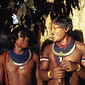 Xingu, Brazil. Two laughing young Kayapo men wearing blue beads, shell necklaces and urucum and genipapo face paint.