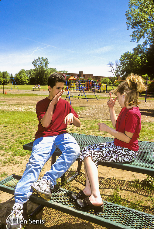 MR / Guilderland, New York. Westmere Elementary School. BOCES deaf and HOH class. Deaf students sign using ASL on playground. Girl: 11, hearing impaired; Boy: 12, Caucasian and Hawaiian American, profoundly deaf. MR: Fis8 Tho7 © Ellen B. Senisi