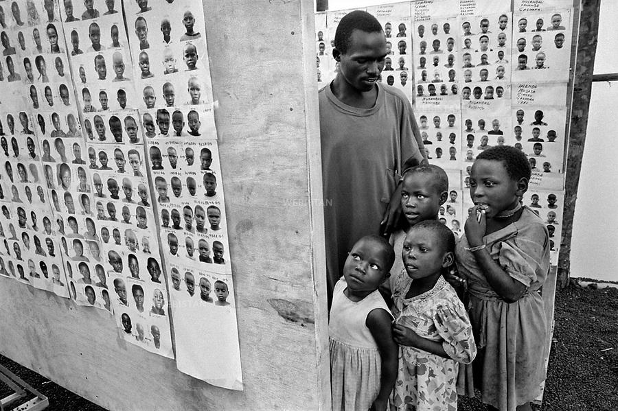 1995. Zaire. Democratic Republic of the Congo (DRC). Nord-Kivu Province. Near Goma. In a camp, Rwandan Hutu refugees who fled their country during the 1994 Rwandan Genocide and who have lost their family, look at portraits of children pined on boards to identify their relatives. Zaïre. République Démocratique du Congo (RDC). Province du Nord-Kivu. Près de Goma. Dans un camp, des réfugiés rwandais hutus qui ont fui leur pays pendant le génocide au Rwanda en 1994, et qui ont perdu leur famille, regardent les portraits d'enfants affichés sur des panneaux pour y reconnaître un membre de leur famille.