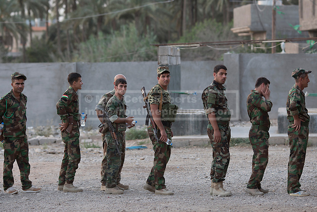 29/06/2014. Khanaqin, Iraq. Kurdish peshmerga fighters stand in line for dinner at a Kurdish peshmerga base in Khanaqin, Iraq.<br /> <br /> The peshmerga, roughly translated as those who fight, is at present engaged in fighting ISIS all along the borders of the relatively safe semi-automatous province of Iraqi-Kurdistan. Though a well organised and experienced fighting force they are currently facing ISIS insurgents armed with superior armament taken from the Iraqi Army after they retreated on several fronts. &copy; Matt Cetti-Roberts