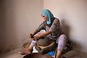 Morocco - Tidzi - Amina Hammoush, 40, grinds the argan nuts to extract the precious oil.
