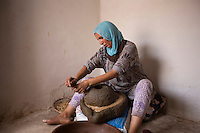 Morocco - Tidzi - Amina Hammoush, 40, grinds the argan nuts to extract the precious oil.