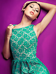 Sensual fashion photo of a young beautiful woman in retro style green dress on purple background