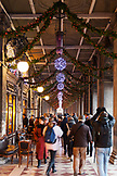 ITALY, Venice. Christmas decorations hangs along the crowded Procuratie Nuove in St. Mark's Square. Caffe Florian is on the left wth some chairs and tables in front of the windows.
