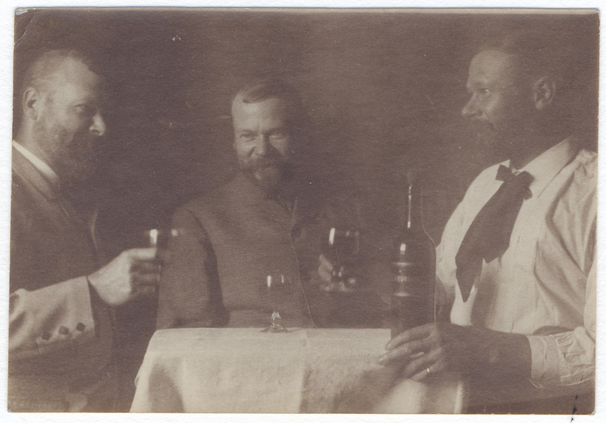 15a.<br /> <br /> (1) 2 1/8 x 3 1/4 [sepia]<br /> (2) 2 3/16 x 3 1/8 [sepia]<br /> <br /> triple of Sam Crone, sharing a bottle of wine at small table; figure in profile in closed jacket with raised glass in right hand, left; three-quarter figure, head in profile, in white shirt with left hand below wine bottle on table and with raised glass in right hand, right; frontal figure in closed jacket with glass on table before him, center.