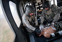 "Medic Staff Sgt. Adam Connaughton and crew chief Sgt. Chad Orozco, with ""Shadow Dustoff"" C/6-101st Avn Rgt, work on an Afghan boy on the way to the hospital at Kandahar Airfield, Afghanistan, September 12, 2010.  He was shot twice with rubber bullets after approaching a base with a toy gun, and the bullets had penetrated his chest. The boy was operated on at the U.S. hospital and was later released."