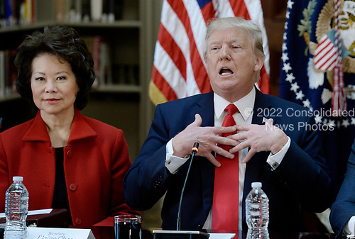 United States President Donald Trump speaks as US Secretary of Transportation Elaine Chao looks on during a strategic and policy discussion with CEOs in the State Department Library in the Eisenhower Executive Office Building (EEOB) in Washington, DC, April 11, 2017.<br /> Credit: Olivier Douliery / Pool via CNP